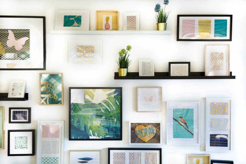 art wall, art display, drawings, photographs, shelves